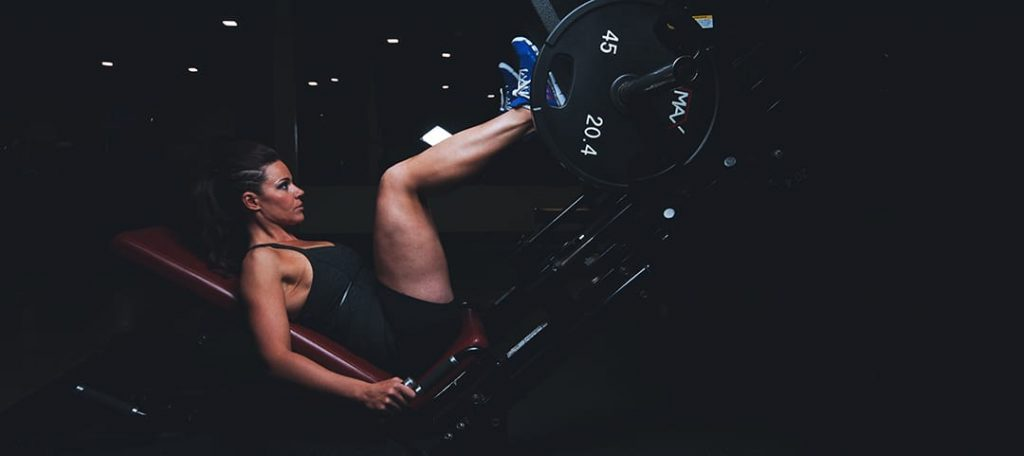 Does Glute Activation Work? What the Science Says at Belle of the Barbell Woman doing Leg Press