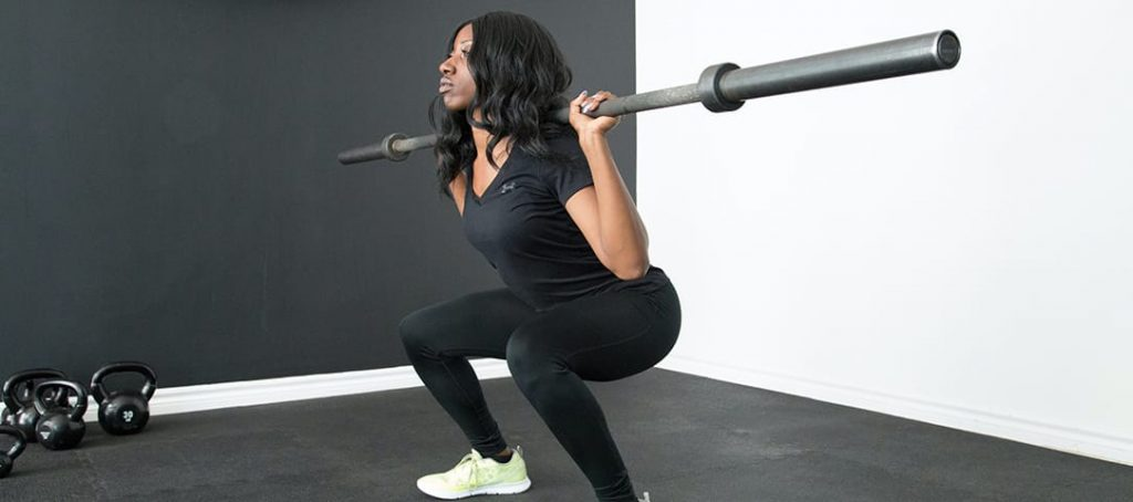 Weight Lifting Warm Up Science Woman Squatting Starting with Light Weight Barbell
